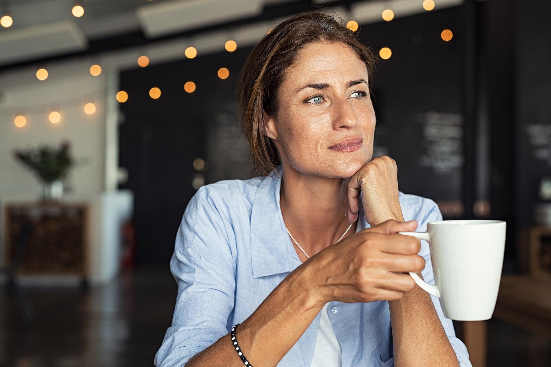Aging woman holding coffee mug