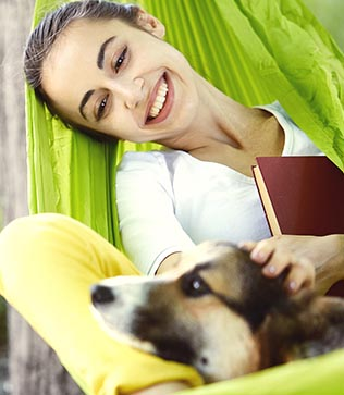 Health woman in hammock with dog