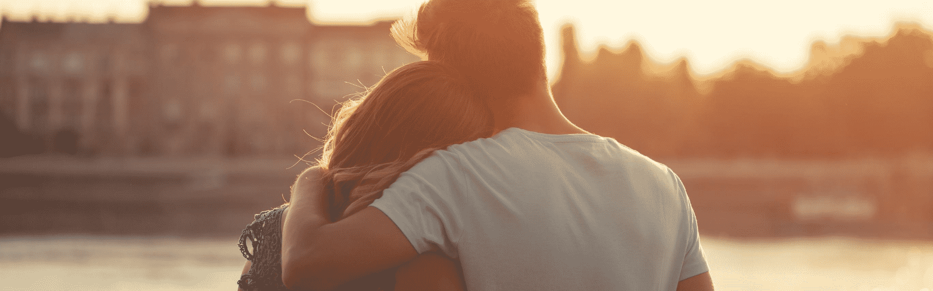 Couple hugging looking into the sunset