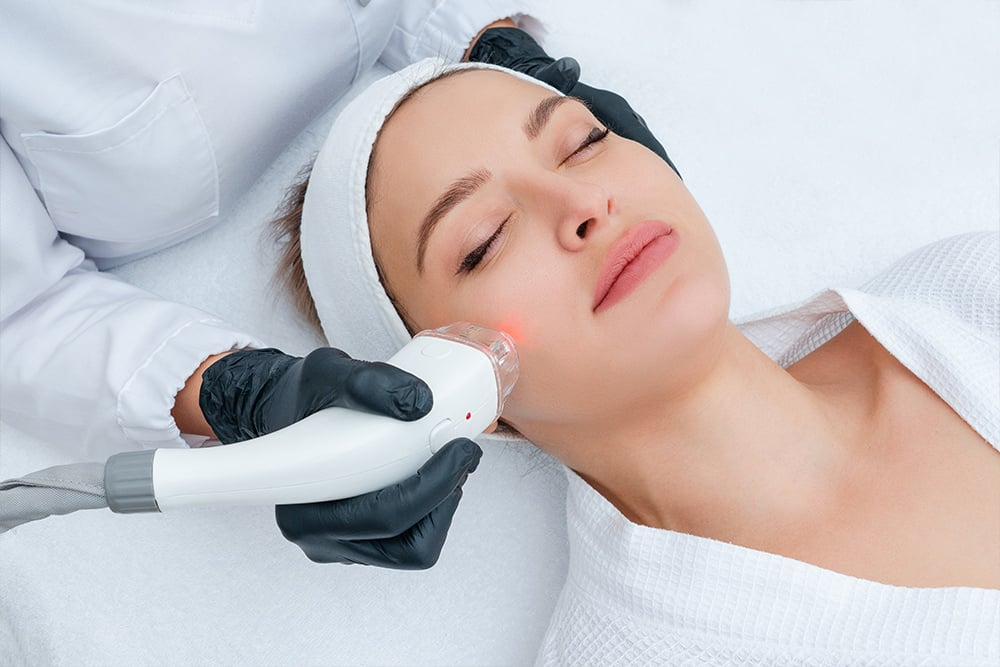 Woman laying down getting procedure to face