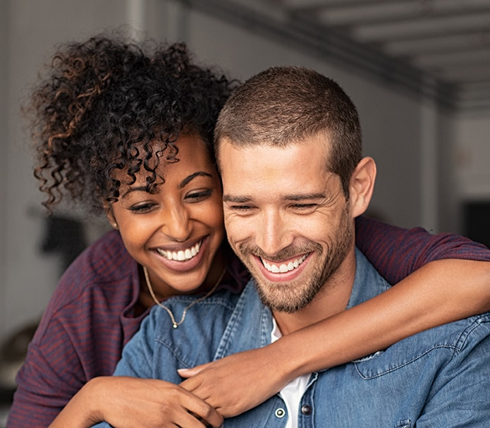 Smiling-young-couple-embracing